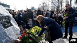 Relatives of Ukrainians who died in plane shot down by Iran attend ceremony unveiling memorial stone. February 17, 2020.