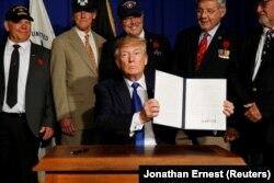 Дональд Трамп тримає указ «Державний план дій з підтримки ветеранів і припинення самогубств серед ветеранів», 5 березня 2019 року