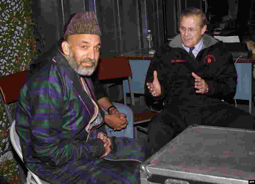 U.S. Defense Secretary Donald Rumsfeld (right) meets with Karzai at Bagram air base outside Kabul on December 16, 2001, six days before Karzai took the oath of office as chairman of the Afghan interim administration. Rumsfeld had arrived at Bagram for a surprise visit, the first by a senior U.S. official to Afghanistan since U.S.-led strikes began against the Taliban in October 2001.