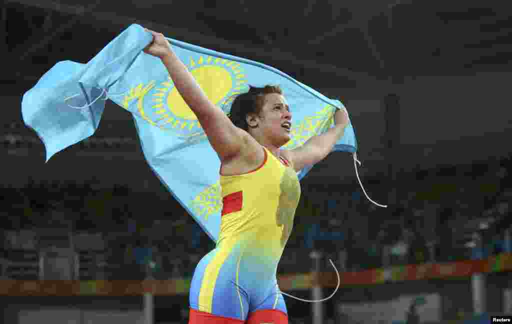 Yekaterina Larionova of Kazakhstan hoists her country's flag after winning bronze in the women's 63kg freestyle wrestling competition.