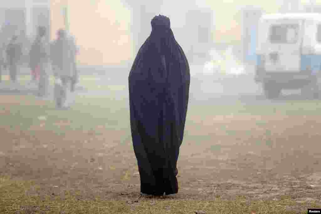A woman wearing a burka leaves a polling booth after voting during state-assembly elections in Uttar Pradesh, India on February 15. (Reuters/Cathal McNaughton)