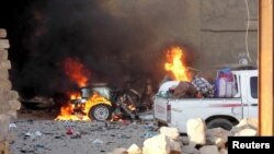 A car is engulfed by flames during clashes in Ramadi on May 16.