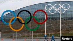 Volonteri prolaze pored olimpijskih krugova ispred ledene dvorane u Olimpijskom parku u Sočiju