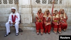 FILE: A groom (L) and four brides sit outside the venue of their weddings as they have arrived late to a mass Muslim marriage ceremony in the western city of Ahmedabad.