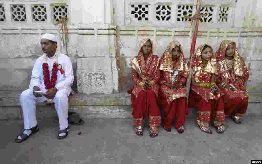 A groom and four brides sit outside the venue of their weddings at a mass Muslim marriage ceremony in the western Indian city of Ahmedabad. (Reuters/Amit Dave)