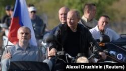 Сергей Аксенов (слева), Михаил Развожаев (за президентом России) и Владимир Путин во время мотопробега «Ночных волков» в аннексированном Севастополе