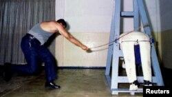 Служащий сингапурской тюрьмы демонстрирует процедуру порки.
