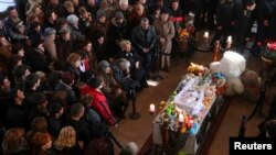 Armenia -- People surround the coffin with the body of six-month-old boy Seryozha Avetisian after he died of his wounds in hospital, following a killing spree last week, during a funeral ceremony in Gyumri January 21, 2015
