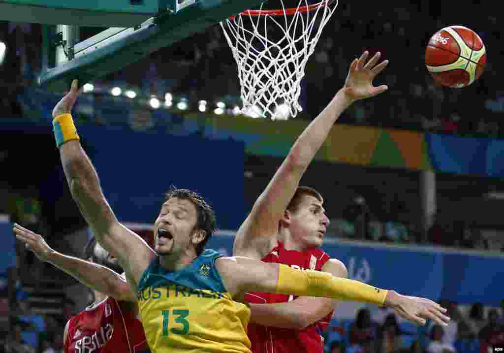 David Andersen of Australia (center) is crowded out by the Serbian defense during their men's basketball semifinal. The Serbs eventually triumphed 87-61.