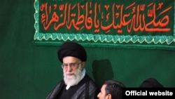 Supreme Leader Ali Khamenei (center) and President Mahmud Ahmadinejad (to his immediate left) during a religious ceremony on May 7