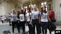 Aktivistet e grupit Femen duke përshëndetur pasi u paraqitën në një gjykatë në Paris