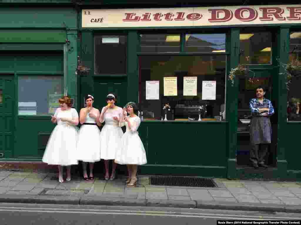 """Ladies in Waiting"" by Susie Stern. Borough Market, London, United Kingdom. ""While exploring Borough Market in London, I was delighted to come across four lovely young women dressed in vintage white dresses, eating ice cream as the local shopkeeper looked on. Are they brides? Or bridesmaids. I don't know, but they are obviously enjoying a very special day."""