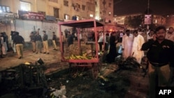 Pakistani security officials scan the site of a bomb blast at a Karachi, which killed at least six people on September 18.