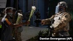 Протестувальник протягує квіти бійцю Національної гвардії, який стоїть поблизу офісу окружного прокурора в місті Лос-Анджелесі. 3 червня 2020 року (Фото AP/Damian Dovarganes)