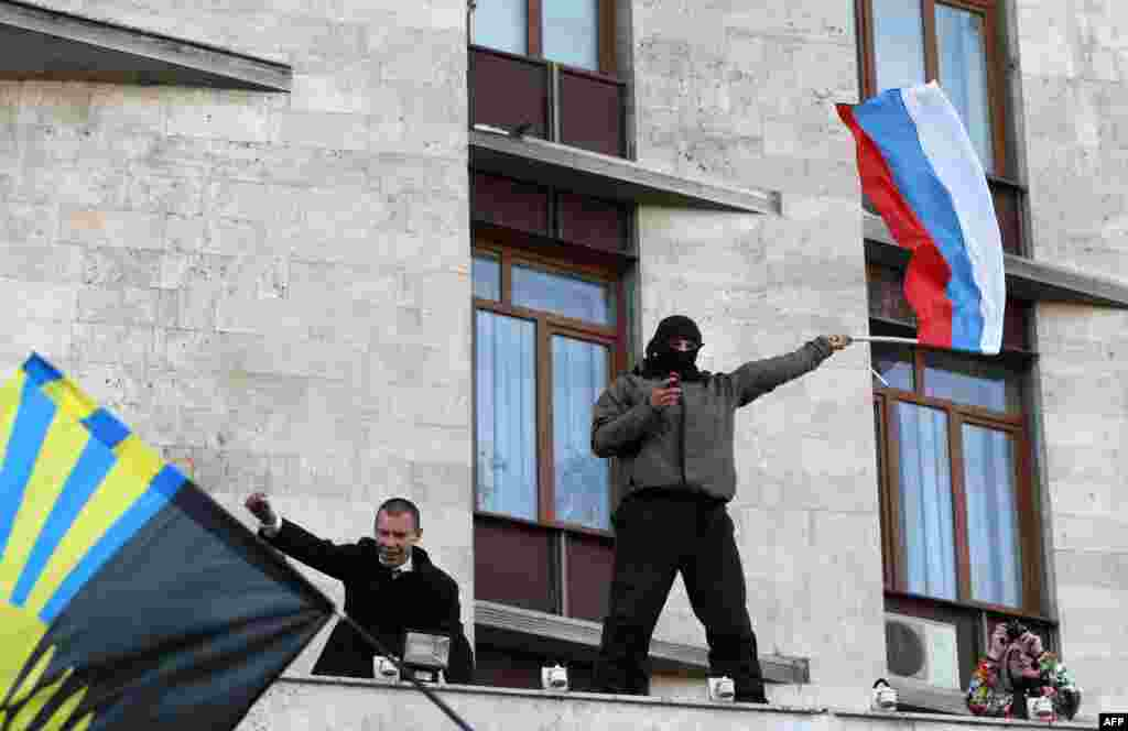 A Pro-Russia supporter waves a Russian flag after storming the regional administration building in Donetsk.