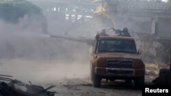 Free Syrian Army fighters fire from the back of a pick-up truck in the Ramous area, southwest of Aleppo, on August 2.