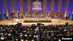 Delegates applaud after the vote at UNESCO headquarters in Paris, where the United Nations' cultural agency decided to give the Palestinians full membership of the body on October 31.