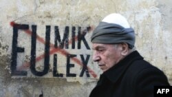 A Kosovar Albanian man walks in front of anti-EU and UN graffiti in the capital, Pristina, in late November.