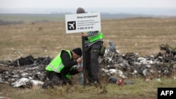 Следователи на месте крушения самолета, выполнявшего рейс MH17 из Амстердама в Куала-Лумпур.