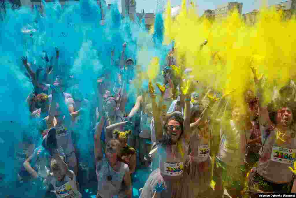 "Participants throw blue and yellow powder in the air during the ""Color Run"" in Kyiv, Ukraine, on June 10. (Reuters/Valentyn Ogirenko)"