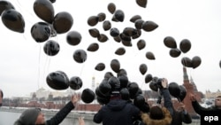 Russian opposition activists and human rights defenders release black balloons in front of the Kremlin to mark the sixth anniversary of the death in prison of lawyer Sergei Magnitsky in Moscow on November 16, 2015.