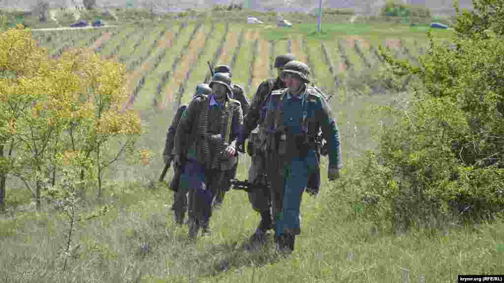 Изображающие немецких солдат реконструкторы возвращаются на позиции