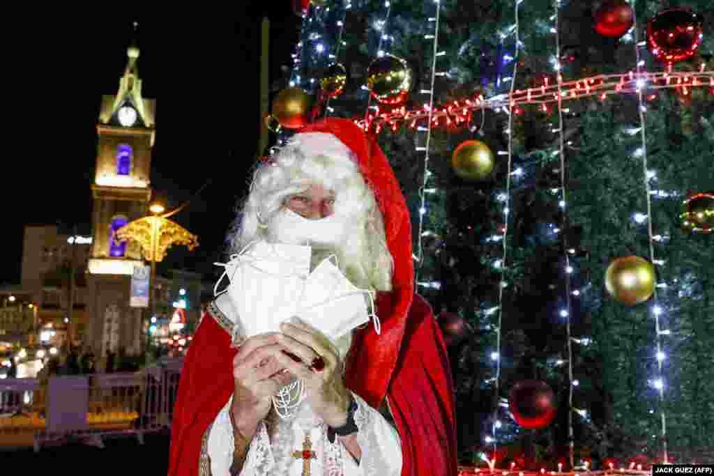 Израиль. Мужчина в одежде Святого Николая раздает защитные маски рядом с рождественской елкой после церемонии зажжения праздничных огней в центре Тель-Авива, 6 декабря 2020 года