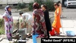 Жители одного из районов Душанбе за неимением доступа к воде в собственных квартирах, набирают воду из дворового водопровода. Фото: июль 2012 года