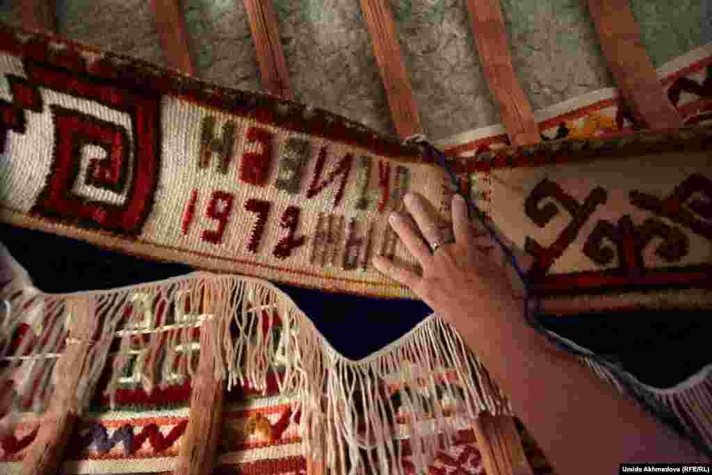 На тканной узорной ленте фотокорреспондент Азаттыка увидела вышивку «1972 год». Астара-апай объяснила, что эта лента — подарок младшей сестры мужа, который она преподнесла семье 44 года назад.
