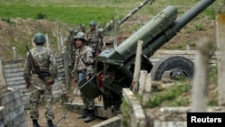 Nagorno-Karabakh -- Ethnic Armenian soldiers stand next to a cannon at artillery positions near the Nagorno-Karabakh town of Martuni, April 7, 2016