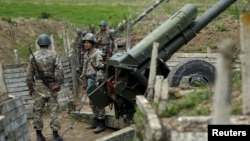 Nagorno-Karabakh -- Armenian soldiers stand next to a cannon at artillery positions near the Nagorno-Karabakh town of Martuni, April 7, 2016