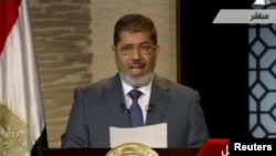 Egyptian President-elect Muhammad Morsi speaks during his first televised address to the nation in Cairo on June 24.