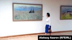 Посетительница выставки художника Молдахмета Кенбаева проходит мимо его картины «Беседа». Алматы, 7 августа 2015 года.