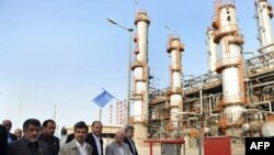 Iranian President Mahmoud Ahmadinejad (C) tours the Abadan oil refinery during the inauguration of a petrol making unit in the southwestern city of Abadan on May 24, 2011 where an accidental blast at the refinery killed one person and wounded 25 during th