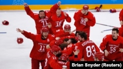 Russian hockey players celebrate after netting the winning goal in overtime to win the gold.