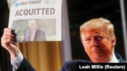 """Президент США Дональд Трамп держит газету USA Today со своей фотографией и заголовком """"Оправдан"""""""