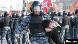 Полицейский тащит участницу демонстрации на Болотной площади. Москва, 6 мая 2012 года.
