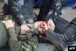 Правоохоронець допомагає товаришу, пораненому під час сутички біля Верховної Ради України. Київ, 31 серпня 2015 року