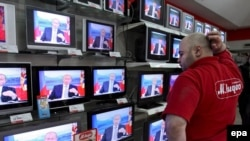 A shop assistant in Moscow watches Vladimir Putin answering questions during a live call-in show in October 2007.
