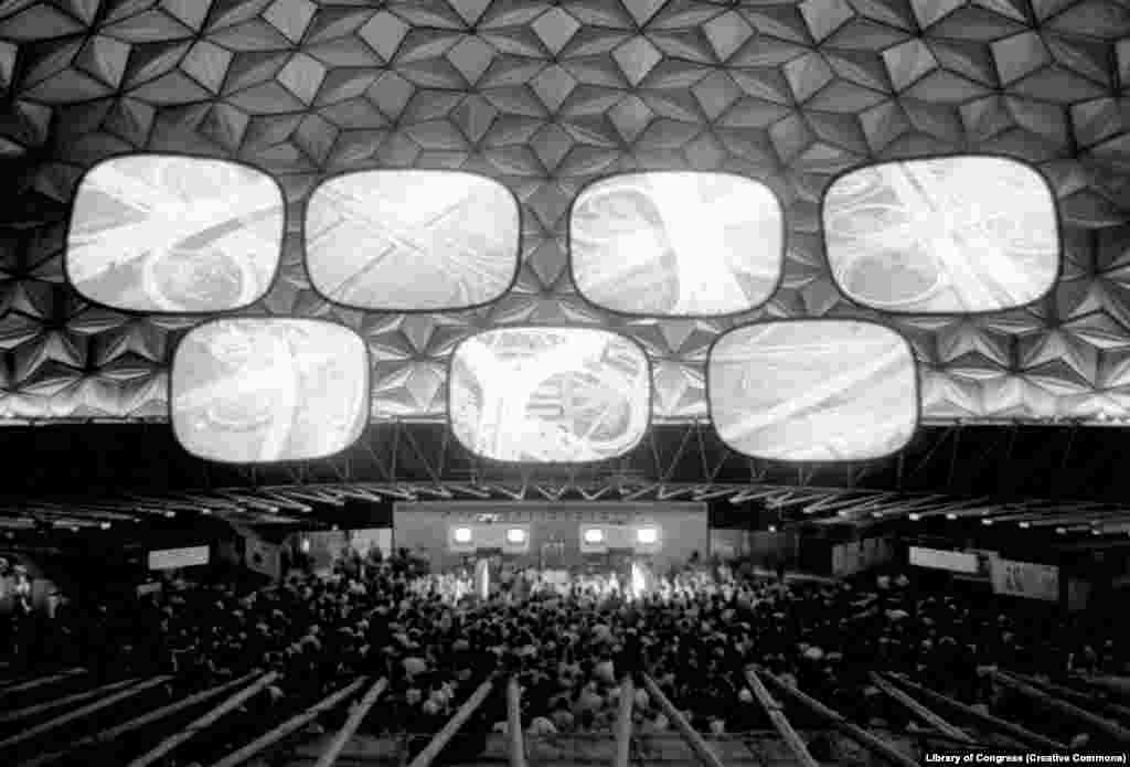 """Huge screens suspended inside a geodesic dome display a film called Glimpses Of The U.S.A. The American exhibition was given just $3.5 million in funding. A member of the design team summed up the frantic preparations for the event: """"Panics and problems. No funds. No budget. No program."""""""