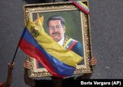 Mbështetësit e presidentit të kontestuar, Nicolas Maduro mbajnë në duar portretin e tij, gjatë një tubimi në Karakas më 1 maj.
