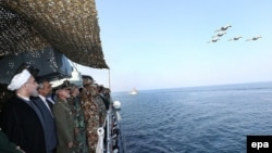 Iranian President Hassan Rowhani (L) attending the navy parade during a military drill in the Oman Sea on December 31.