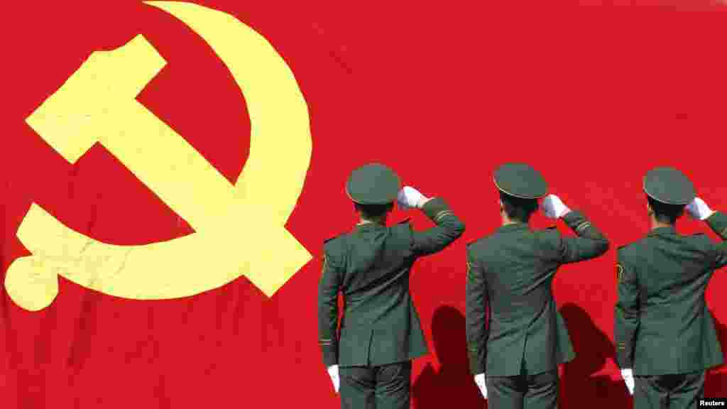 Paramilitary policemen hold their fists in front of a flag of the Communist Party as they attend an oath-taking rally to ensure the safety of the 18th National Congress of the Communist Party, at a military base in Hangzhou.