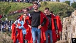 Tradiționala plimbare pe zidul de lângă mare a studenților de la St Andrews Univerity , Scoția, Marea Britanie