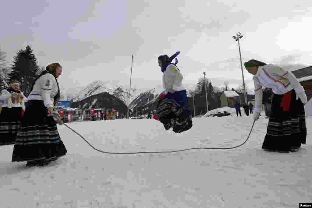 Жінки у традиційному вбранні розважаються біля місця змагань із лижного кросу й біатлону