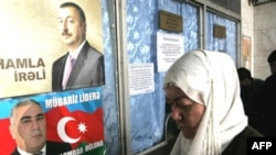 A woman stands near election posters for current Azerbaijani President Ilham Aliyev