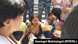 Женщины сидят на ступенях лестницы в Нур-Султане после того, как полицейские перегородили им путь.