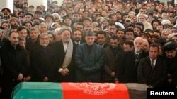 Afghan President Hamid Karzai (center) prays near the flag-draped coffin of Afghan Vice President Marshal Mohammad Qasim Fahim during his burial ceremony at the Presidential Palace in Kabul on March 11.