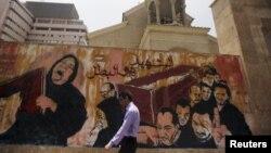 Человек у стены с граффити, изображающими траурную процессию. Иллюстративное фото.