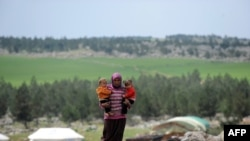 لاجئة تحمل طفليها في منطقة عفرين